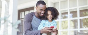 Father and daughter using cellphone on porch to look up where to get a major purchase loan