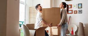 Couple carrying a big box together, moving into their new home