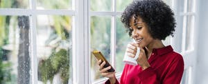 Woman at home drinking cup of coffee and looking up the 2020 standard deduction on her cellphone
