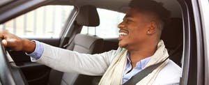 Smiling man driving car that was financed with Acura Financial Services