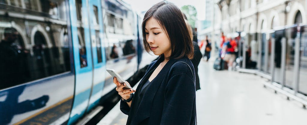 Woman at train station, looking up the Electronic Fund Transfer Act on her cellphone