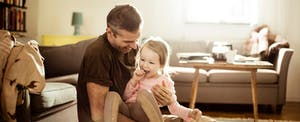 Smiling father holding young daughter in living room