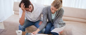 Couple in living room, looking stressed and looking for mortgage relief programs