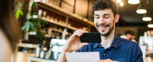 Young man sitting in cafe, looking at check information as he makes a mobile deposit on his phone