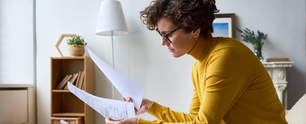 Woman sitting at home looking at documents she needs for filing back taxes