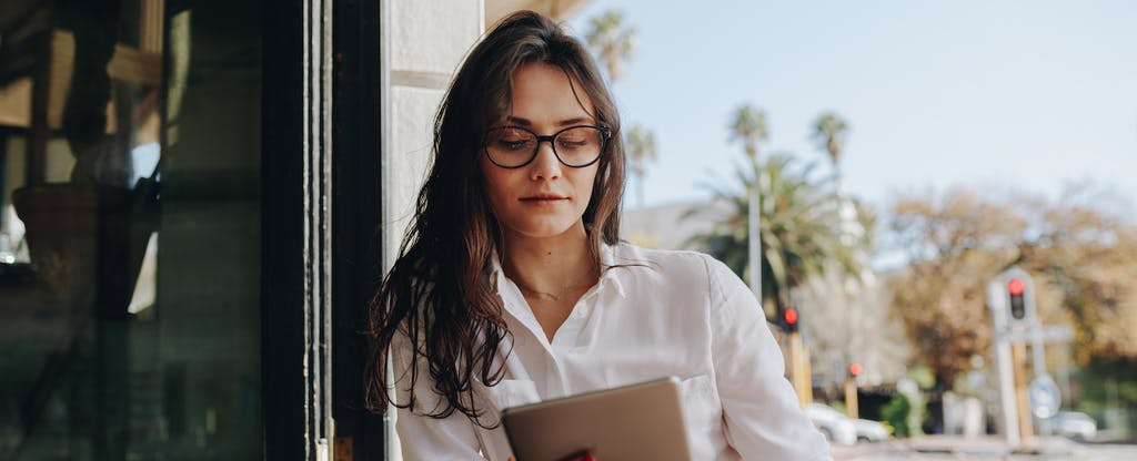 Woman outside with digital tablet, looking up how to open a second chance checking account
