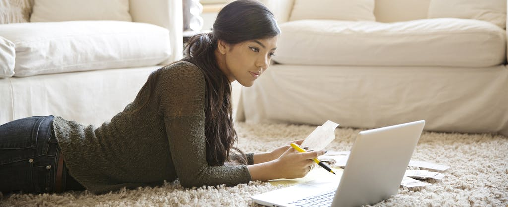 Woman lying on the floor of her living room with her laptop open, considering her student loan debt relief options