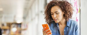 Woman looking at cellphone to read about the consequences of depositing a fake check