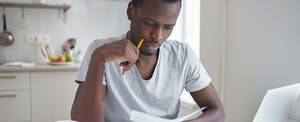 Man looking at check and holding a pencil.