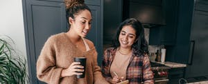 Two women standing in kitchen, looking up mortgages with newfi lending