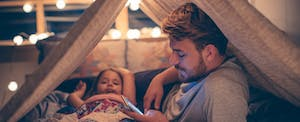 Father at home with daughter, looking up Sebonic Financial mortgages on his cellphone