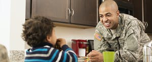 Father in military uniform in kitchen with young son in their home that they financed with a veterans united mortgage