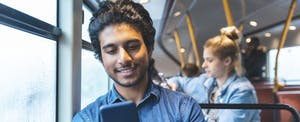 Young man on bus, looking up his ABA number on his cellphone
