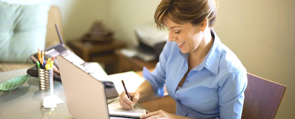 Woman at desk writing check