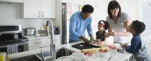 Family baking cookies in kitchen of their new home