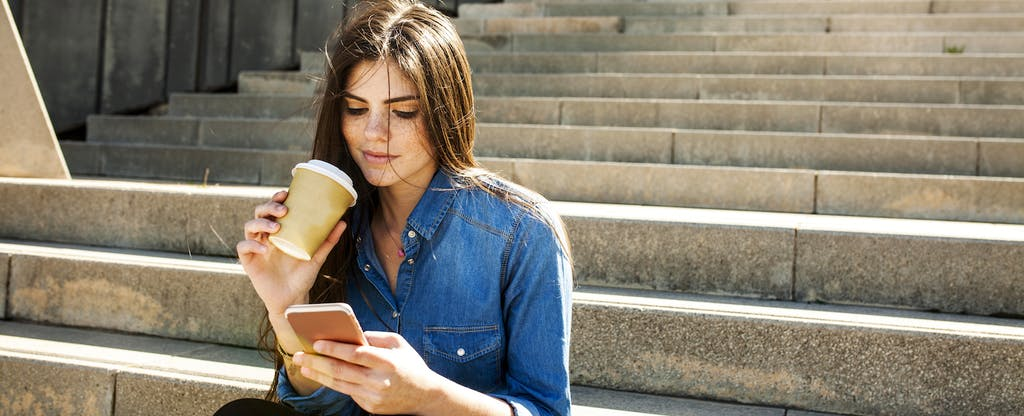 Young woman with coffee sitting outside on stairs, using cellphone to look up current balance vs available balance