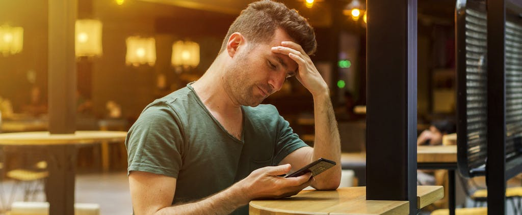 Man using cellphone to look up what is a negative bank account