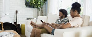 Couple relaxing watching TV in the living room of their new home