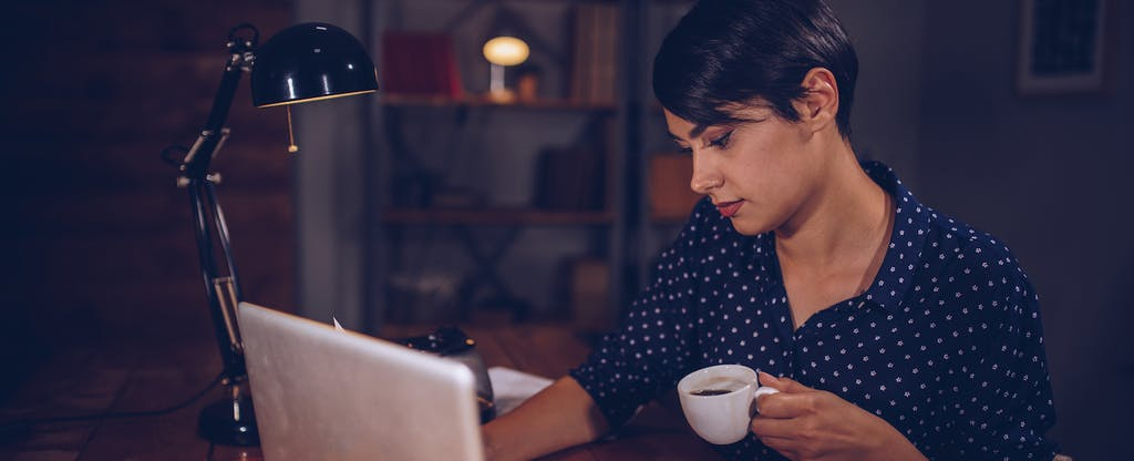Young woman sitting at home, drinking coffee and reading on her laptop about the latest stimulus check for Americans