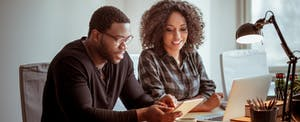 Man and woman sitting at desk with digital tablet, looking up what is home equity