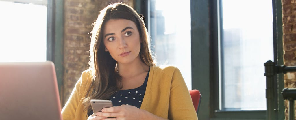 Young woman holding her cellphone and wondering if checking accounts are free