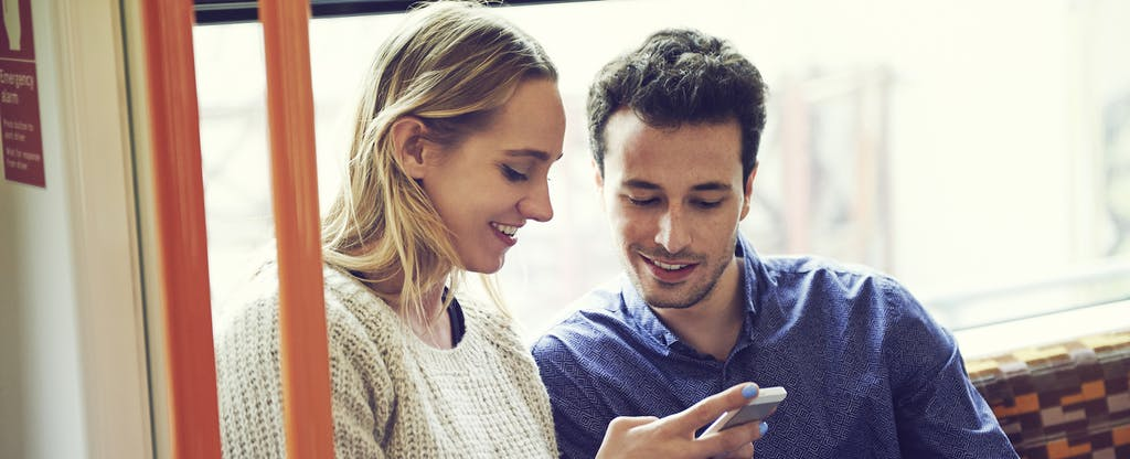 Couple on train using smartphone, looking up the best car buying apps