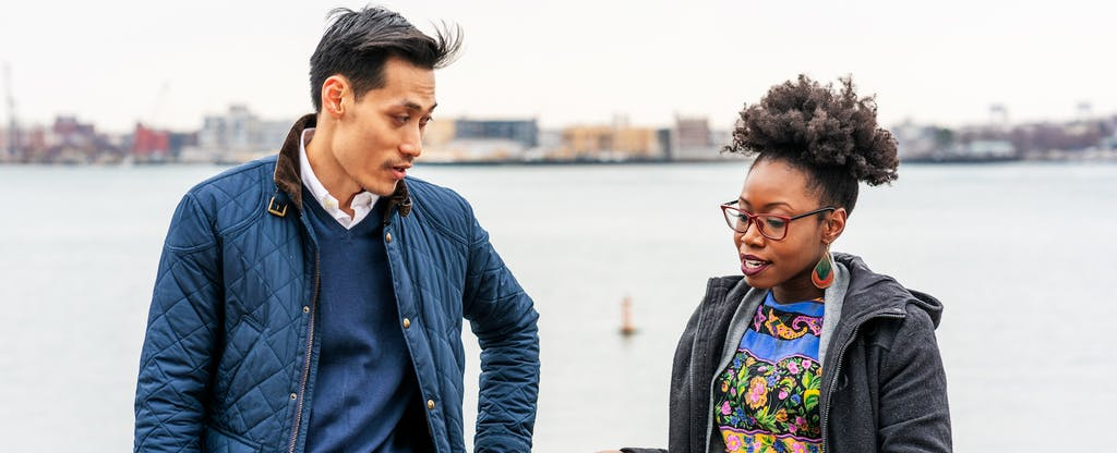 Man and woman standing together on a bridge, discussing lending discrimination