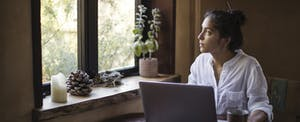 Young adult woman sitting at table with a cup of tea, using her laptop to look up eagle finance