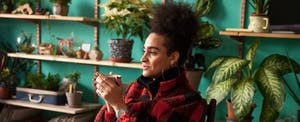 Woman sitting drinking a cup of coffee in a room with plants