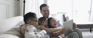 Father and young children taking on a sofa, playing educational math and finance games on a digital tablet
