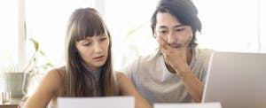 couple examining document with laptop
