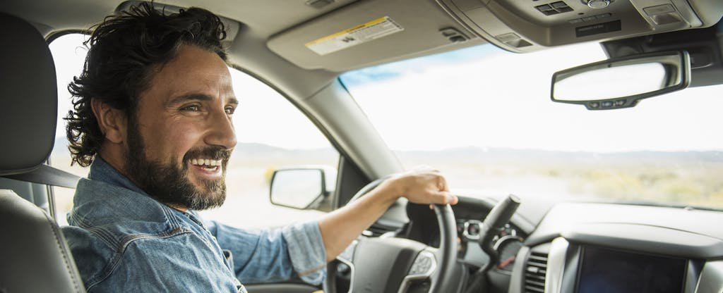 Man inside car at the wheel smiling