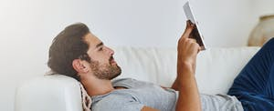 Young man shopping on the internet on a digital tablet while lying back on his sofa at home.