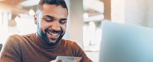Smiling young man holding a credit card and using laptop to look up buy now pay later apps