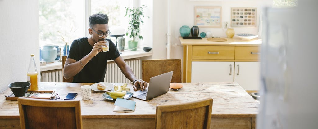 Man sitting at home, eating breakfast and reading on his laptop about cash management accounts