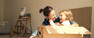 Laughing woman with daughter sitting in cardboard box in their new home they are moving into