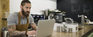 Coffee shop owner working on laptop