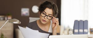 Young woman with glasses on at her desk, looking at her budget and financial paperwork