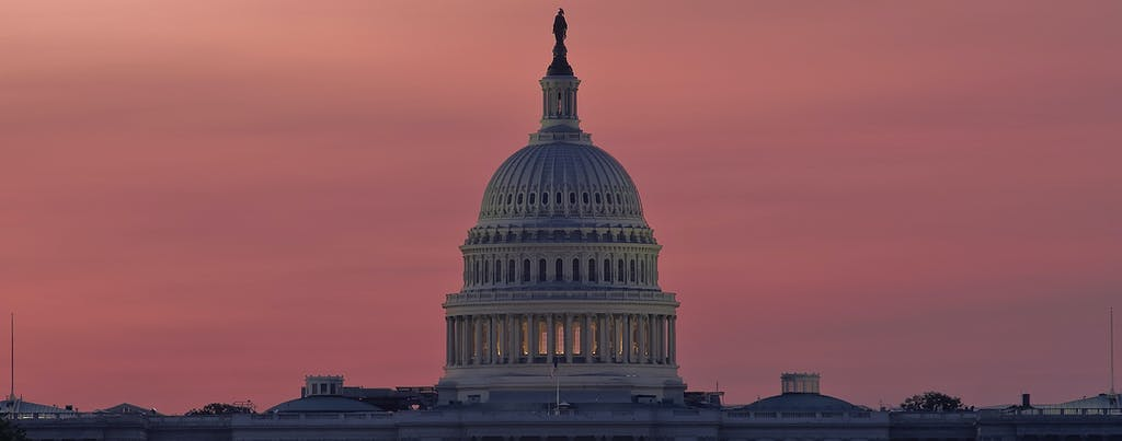 U.S. Capitol building at dawn, in front of an orange and rose-colored sky.