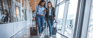 Two women with suitcases walking through airport and talking