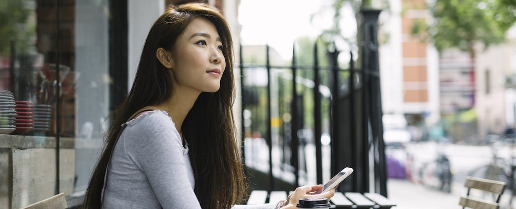 Young woman sitting outside of her apartment, looking up companies like affirm on her cellphone