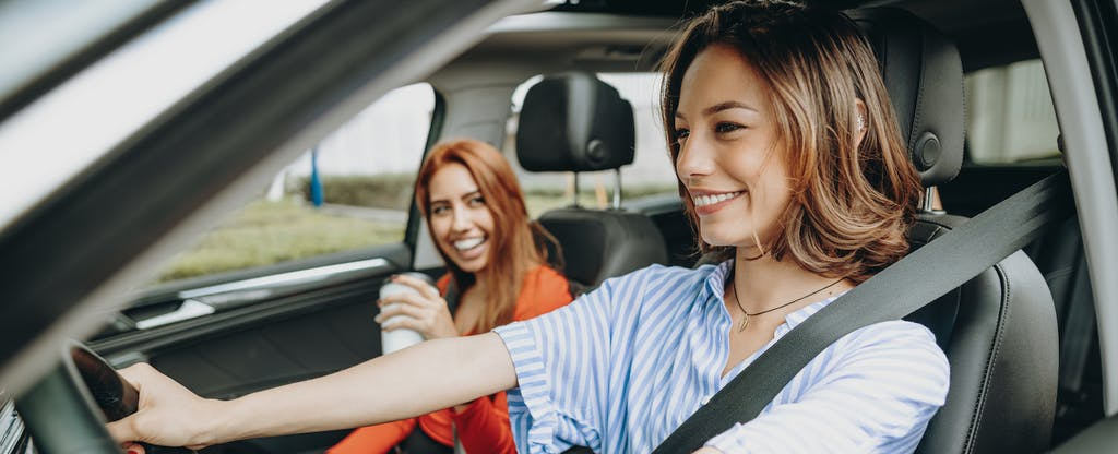 Two smiling women driving with car windows rolled down