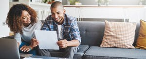 Young couple at home, using laptop to apply for a consumer direct mortgage