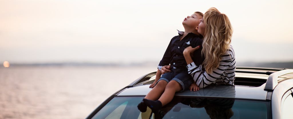 woman with a child sitting on a car looking at the sky