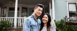 Young couple in front of their new Massachusetts home