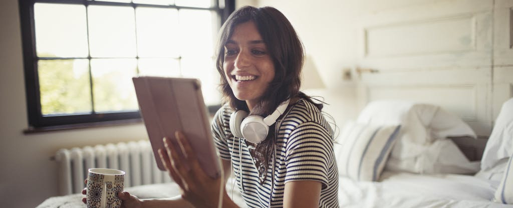 Smiling woman sitting on bed, drinking coffee and looking up what is a bank statement on her digital tablet