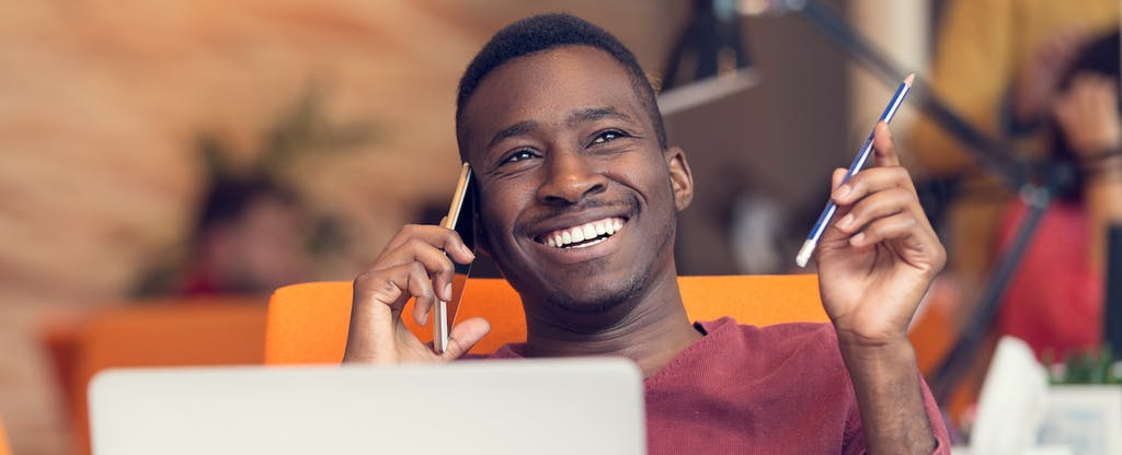 Man using his laptop at home, smiling and talking on the phone as he researches demand deposit accounts