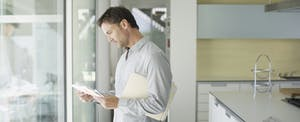 Man looking through mail and papers at home
