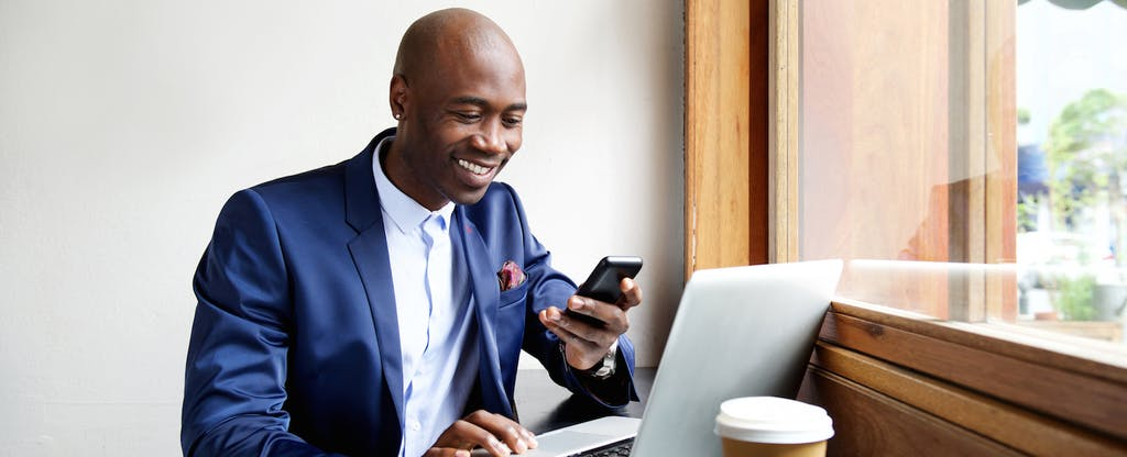 Man sitting at a cafe, using his laptop and smiling at his phone