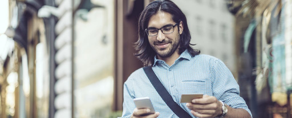 man holding phone and credit card smiling